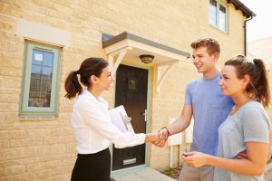 Real,Estate,Agent,Shaking,Hands,With,New,Property,Owners